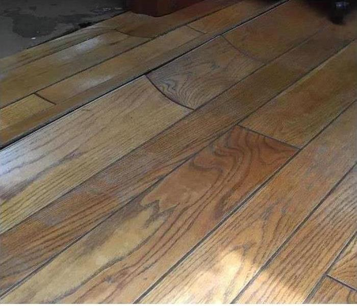 The hardwood floor is bent inwards because of water damage